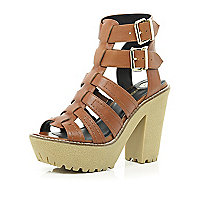 Tan cleated sole gladiator platforms