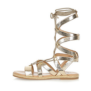 Metallic gold lace-up gladiator sandals