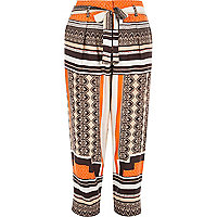 Orange print tapered trousers