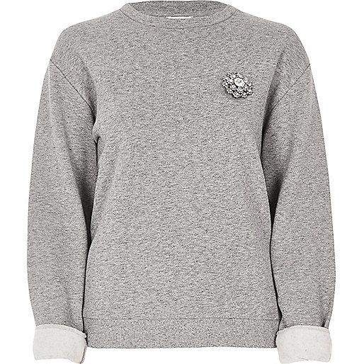 Grauer Pullover mit Brosche