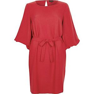 Robe rouge nouée à la taille à manches longues