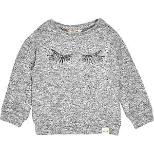 Grauer Pullover mit Paillettenwimpern