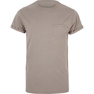 T-shirt marron à poche et manches retroussées.