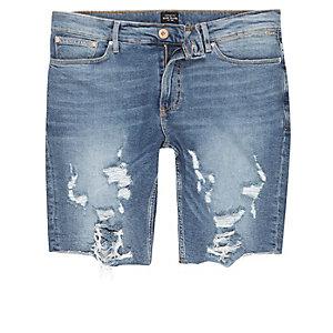 Mid blue distressed raw hem denim shorts