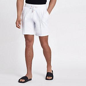Witte slim-fit short met plooitjes en geborduurde wesp