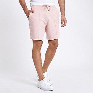 Roze slim-fit short met plooitjes en geborduurde wesp