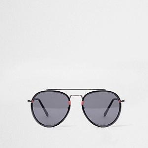 Zwarte ovale pilotenzonnebril met rood accent en getinte glazen