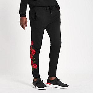 Criminal Damage – Pantalon de jogging noir à rose brodée