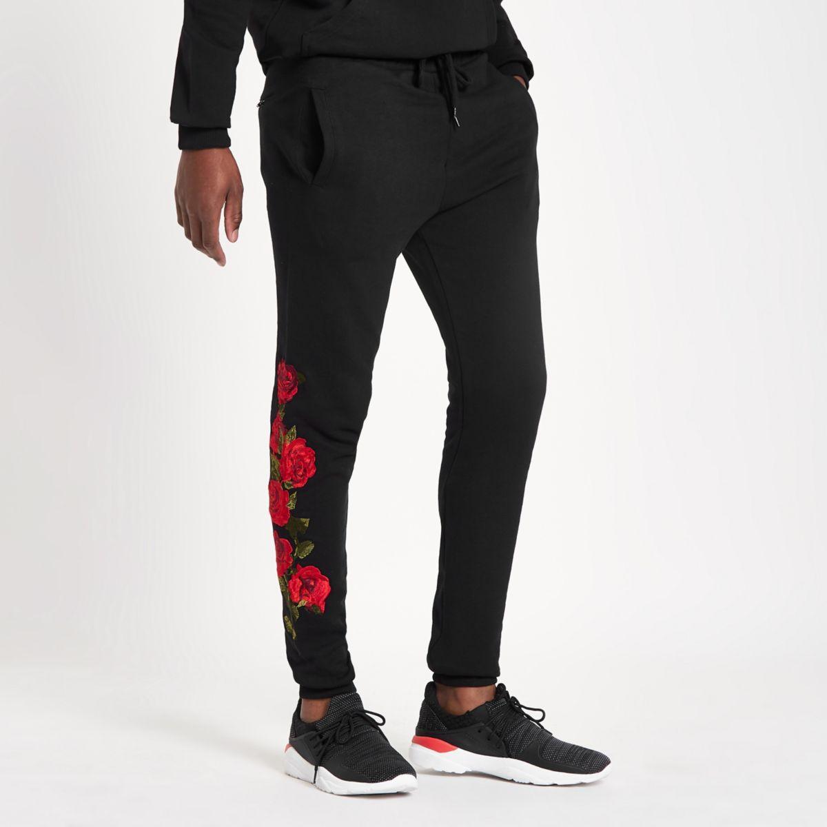 Criminal Damage – Pantalon de jogging noir avec roses brodées