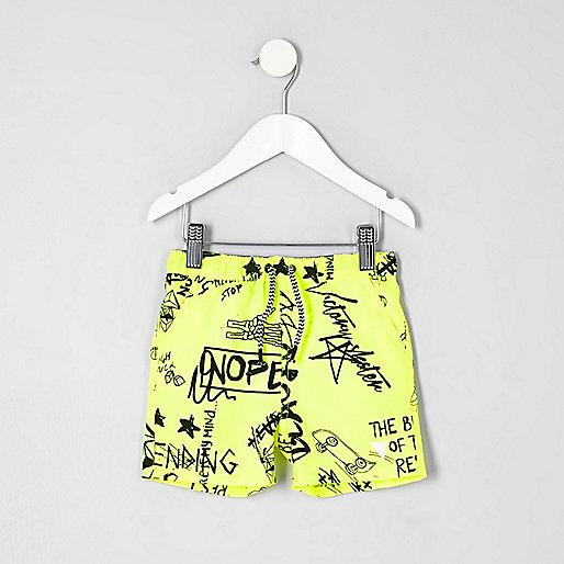 Mini boys yellow graffiti print swim shorts