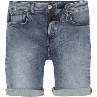 River Island Dylan - Short en jean slim bleu moyen pour garçon - Milieu lavage bleu denim Coupe cintrée Cinq poches Ourlets roulés Passants pour ceinture Fermeture à boutons et fermeture Éclair