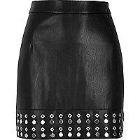 Mini-jupe en cuir synthétique noire avec ourlet orné