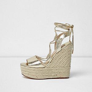 Chaussures dorées à plateforme style espadrilles et talons compensés avec liens