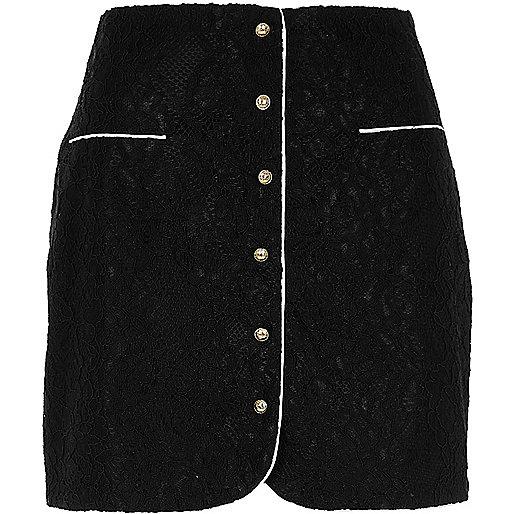 Mini-jupe en dentelle noire boutonnée sur le devant