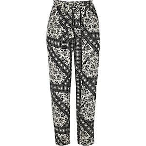 Pantalon fuselé imprimé fleurs noir noué à la taille