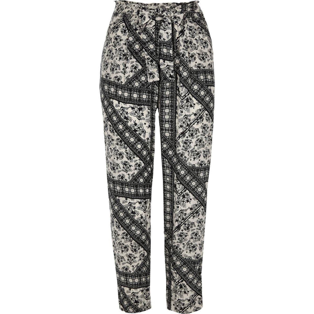 Zwarte smaltoelopende broek met bloemenprint en strikceintuur