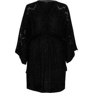 Robe noire avec taille cintrée et manches larges brodées