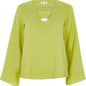Limoengroene blouse met klokkende mouwen en gedraaide achterzijde