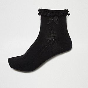 Schwarze Stricksocken mit Zopfmuster und Rüschen