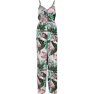 Roze jumpsuit met tropische bladprint en strik op de rug