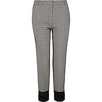 Pantalon cigarette à motif géométrique noir et blanc avec ourlet en dentelle