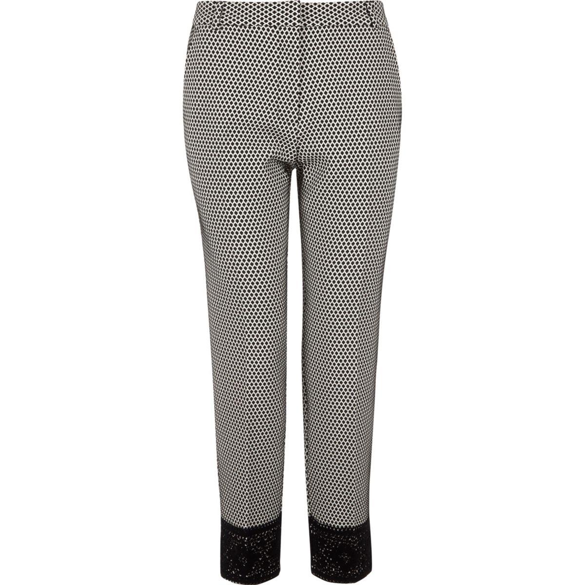 Zwart-witte smaltoelopende broek met kanten zoom en geoprint