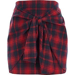 Mini-jupe à carreaux rouge nouée sur le devant