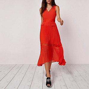Oranje jurk met plooirok en kanten zoom
