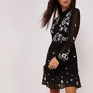 Zwarte hoogsluitende jurk met geborduurde bloemen