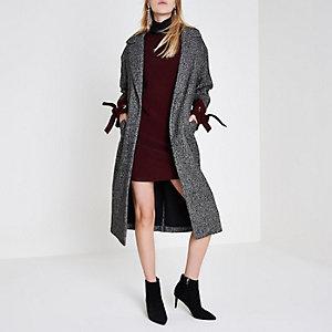 Zwarte jas met visgraatmotief en strikje aan de manchetten
