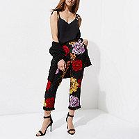 Petite – Schwarze, kurz geschnittene Hose mit Blumen und Quasten