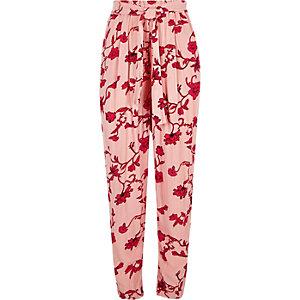 Roze smaltoelopende broek met bloemenprint en strikceintuur