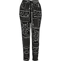 Zwarte smaltoelopende broek met zwart-witte sjaalprint
