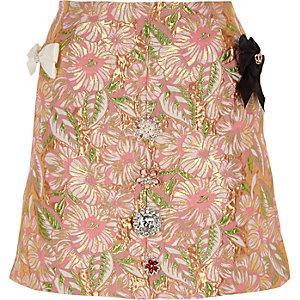 Mini-jupe en brocard à fleurs rose ornée