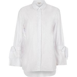 Chemise blanche à manches longues nouées aux poignets