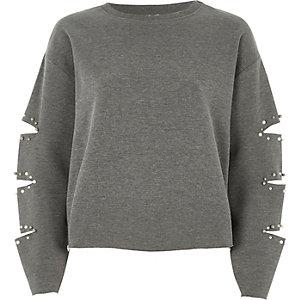 Grijs sweatshirt met scheuren in de mouwen en pareltjes
