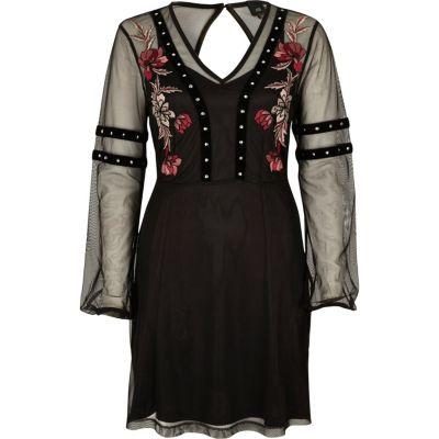 Zwarte geborduurde jurk van mesh met studs aan de zoom