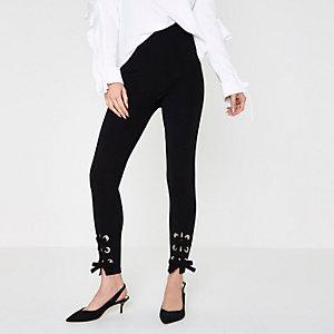 Zwarte legging met oogjes en vetersluiting bij de zoom