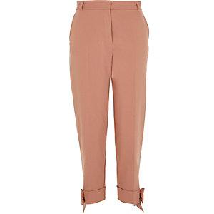 Pantalon cigarette rose avec nœuds à l'ourlet
