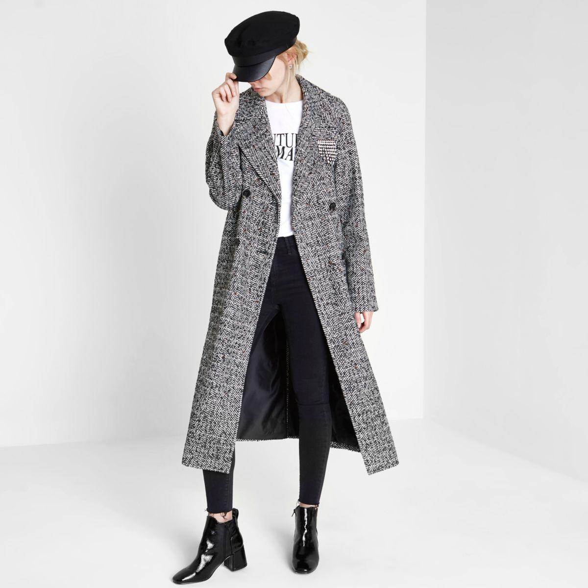 Zwarte lange jas met dubbele knopenrij en broche