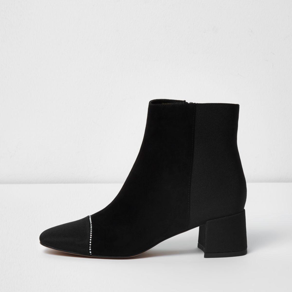 Zwarte laarzen van imitatiesuède en detail op de neus