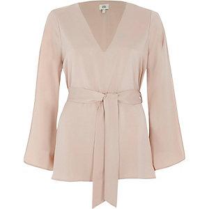 Lichtroze blouse met V-hals en strikceintuur