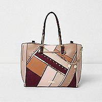 Roze ruime handtas met studs, uitsnedes en bedeltjes