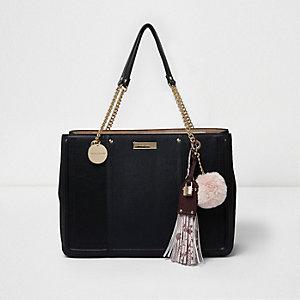 Zwarte handtas met kwastje, structuur en schakels aan handvat