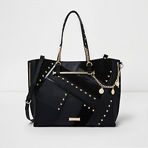 Zwarte ruime handtas met studs, uitsnedes en bedeltjes