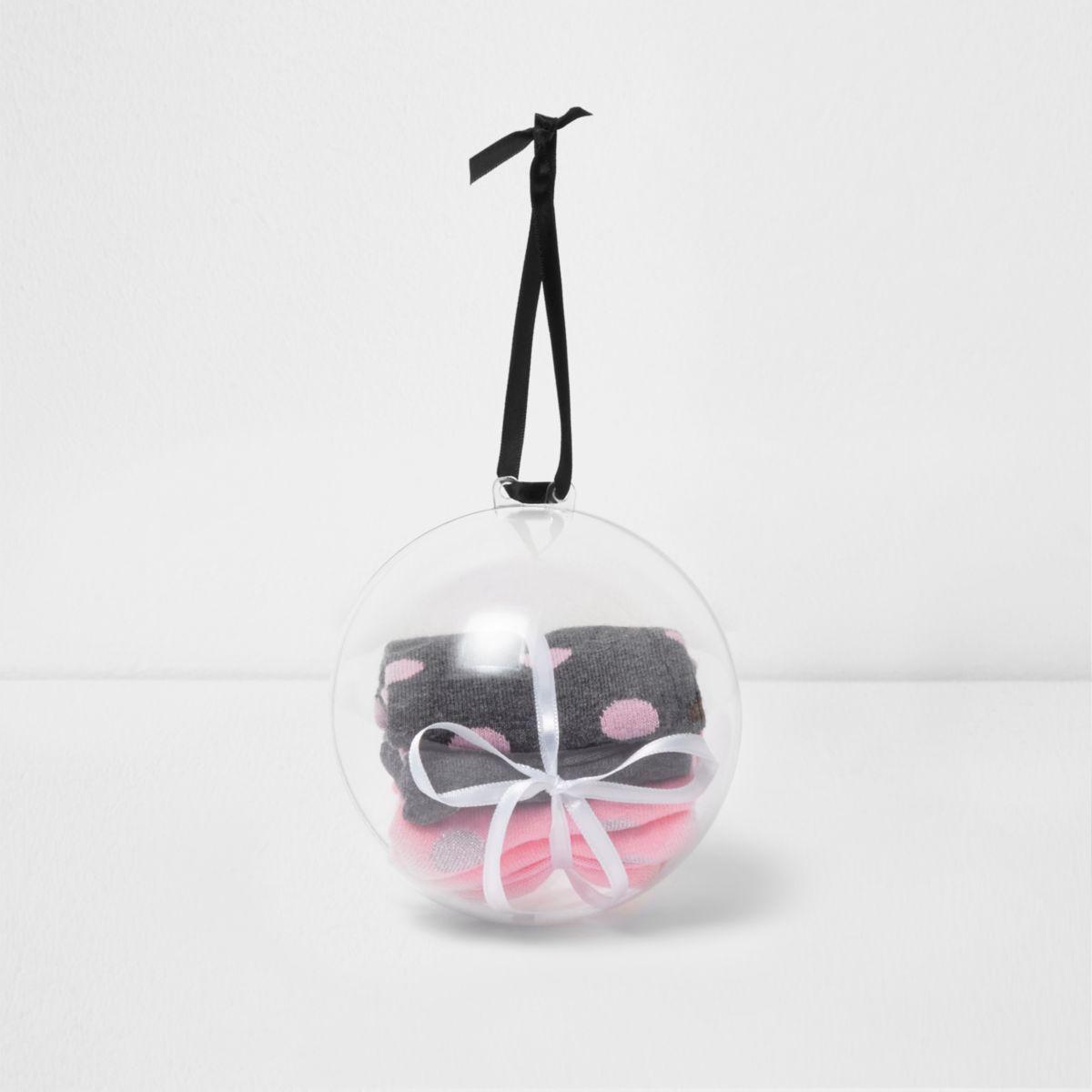 Cadeauverpakking van kerstbal met zwarte en roze sokken