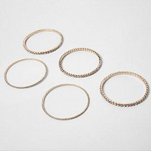 Set met goudkleurige armbanden met siersteentjes