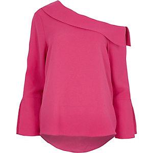 Roze top met lange wijduitlopende mouwen en blote schouder