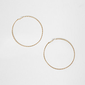 Gold tone faceted oversized hoop earrings