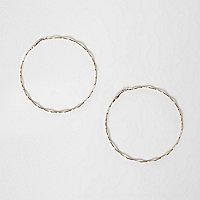 Gold tone thin wavy hoop earrings
